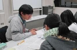 みなみラウンジでの外国につながる子どもたちの 学習支援教室」で指導にあたる山口さん(写真:左
